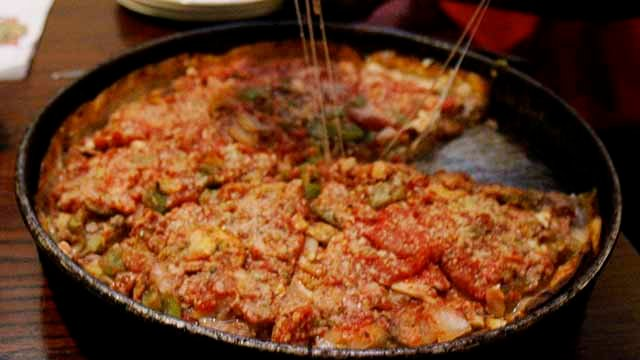 This March 30, 2007 file photo shows a server dishing up a slice of deep dish pizza at Lou Malnati's Pizza in Chicago. The 1 1/2 inch thick legendary pie, loaded with sausage, mushrooms, pepperoni, onions was invented in Chicago