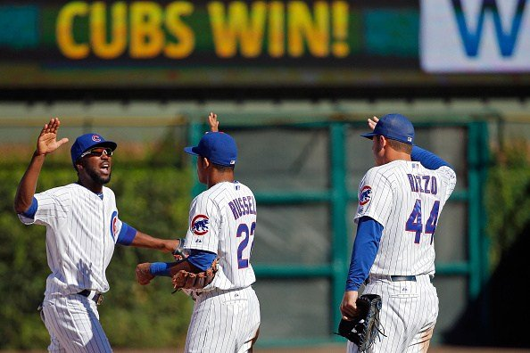 Dexter Fowler #24 of the Chicago Cubs (L), Addison Russell #22 and Anthony Rizzo #44 celebrate their win over the St. Louis Cardinals at Wrigley Field on September 19, 2015 in Chicago, Illinois. The Chicago Cubs won 5-4. (Photo by Jon Durr/Getty Images)